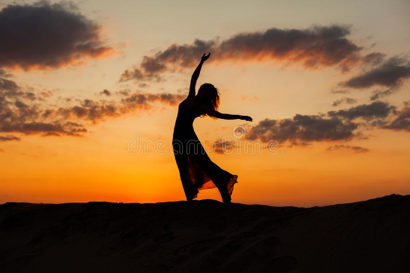 Silhouette of a dancing woman. Silhouette of a dancing woman at sunset in the desert stock images