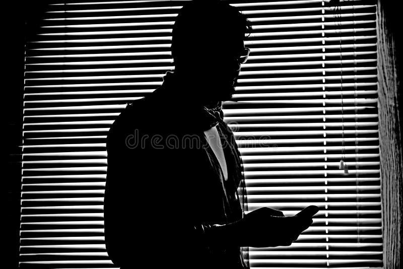 Silhouette dans le monochrome de l'homme avec son iPhone de téléphone portable dans l'obscurité images libres de droits