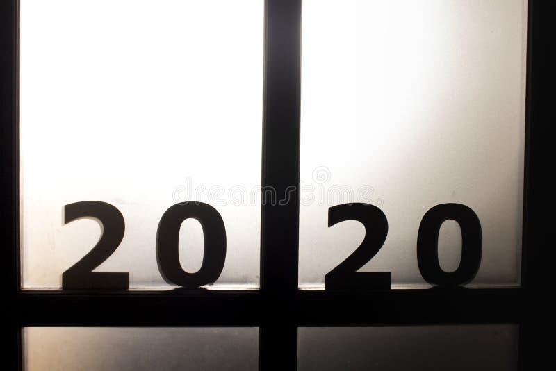 Silhouette date 2020 davanti alla porta di fronte a un'anomala luce del sole, concetto di nuovo anno e paura del futuro fotografia stock