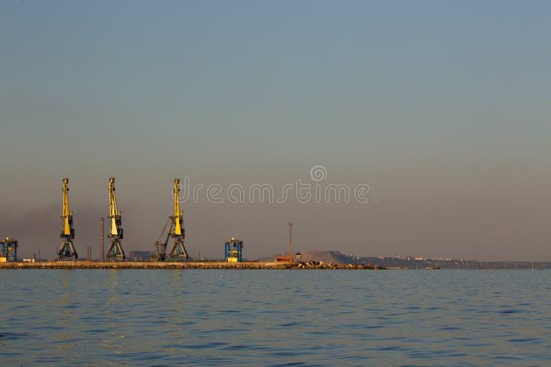 Silhouette de beaucoup grande de grues dans le port à la lumière d'or du coucher du soleil Mariupol, Ukraine image libre de droits