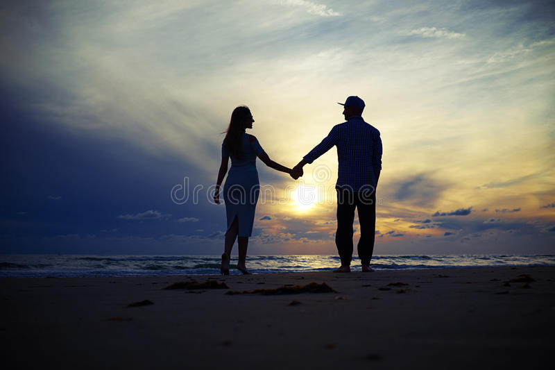 Silhouette de beaux couples fascinants tenant des mains aux uns photos libres de droits