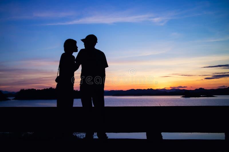 Silhouette de beaux couples sur le lac images stock