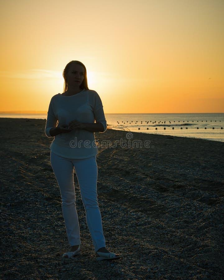 Silhouette de belle femme dans le pantalon blanc et la veste blanche à l'arrière-plan de la mer de coucher du soleil photographie stock