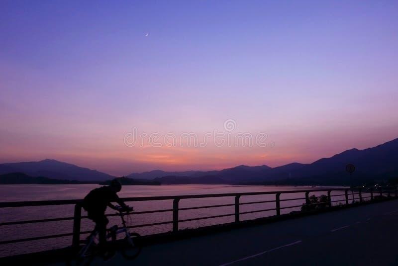 Silhouette de bicyclette, barrière, montagne, ciel de pourpre de gradient images libres de droits