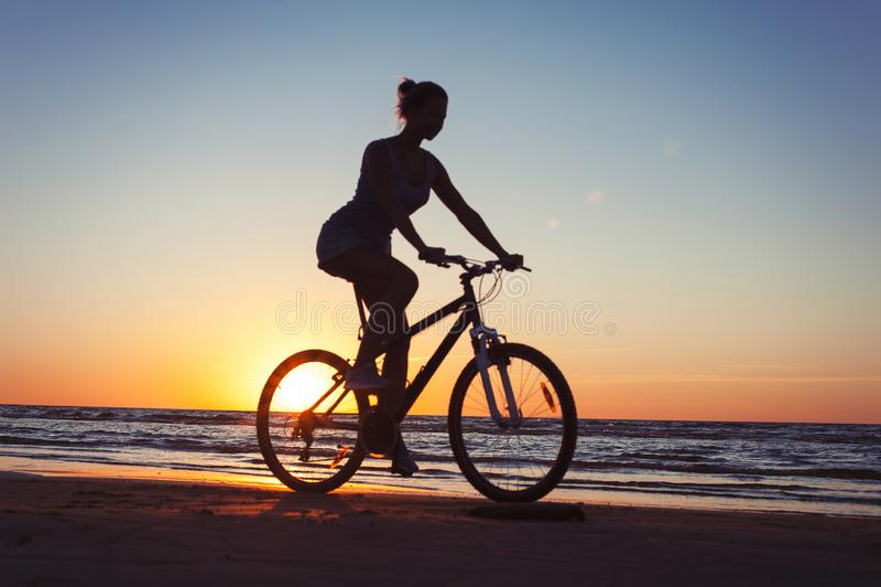 Silhouette de bicyclette sportive d'?quitation de femme sur le fond multicolore de coucher du soleil photos libres de droits