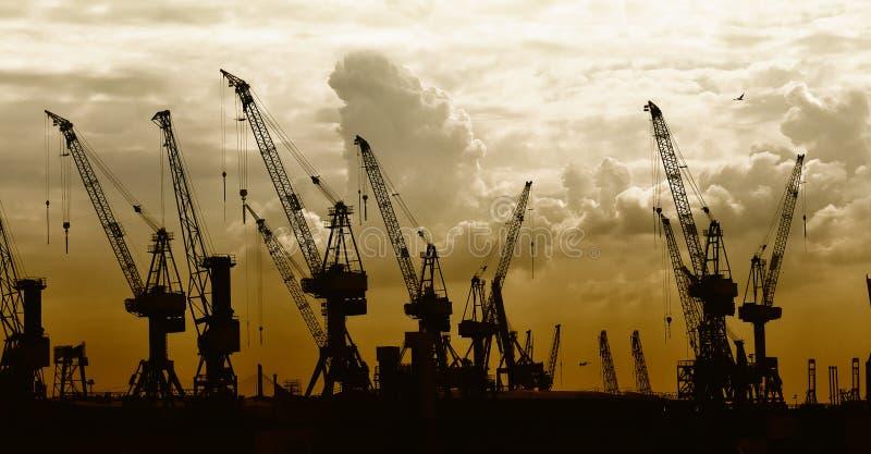 Silhouette de construction des grues sur le coucher du soleil   photographie stock