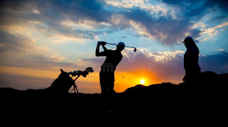 Silhouette de couples de golfeur au coucher du soleil photos stock