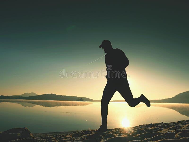 Silhouette de coureur sportif pulsant sur la plage contre le lever de soleil photos libres de droits
