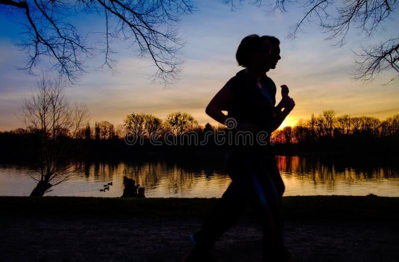 Silhouette de course de l'homme et de femme ensemble sur un coucher du soleil sur la côte de lac photos stock
