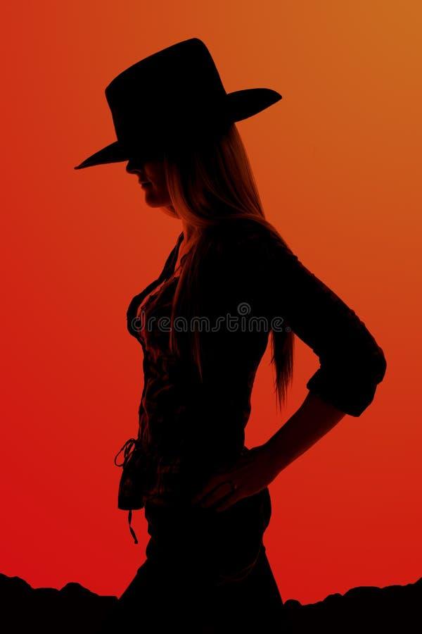 Silhouette de cow-girl avec des mains sur ses hanches photos stock