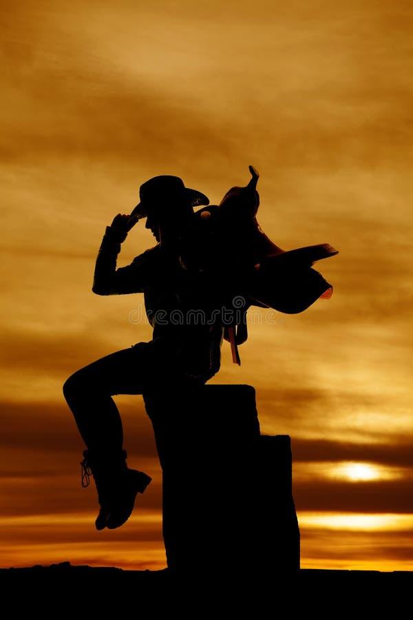 Silhouette de cow-girl avec la selle sur son lookin se reposant d'épaule images stock