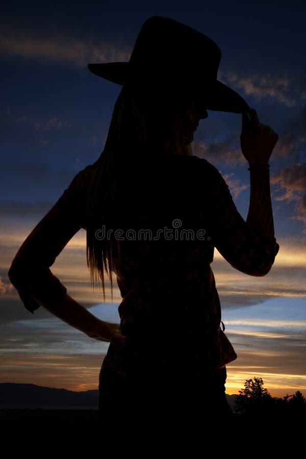 Silhouette de cow-girl inclinant son chapeau au coucher du soleil photos libres de droits