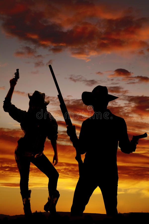 Silhouette de cow-girl supportant l'arme à feu dans le ciel images stock