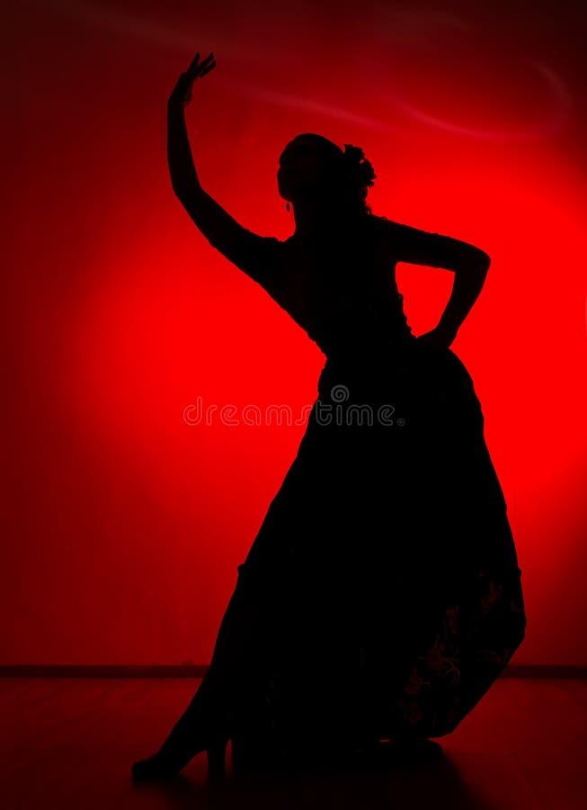 Silhouette de danseur espagnol de flamenco de fille sur un fond rouge photo libre de droits