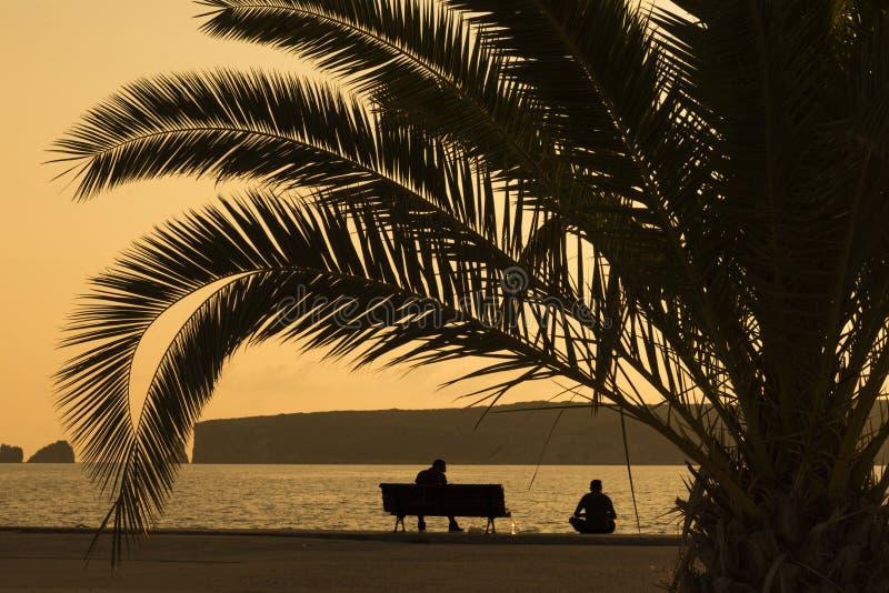 Silhouette de deux amis s'asseyant au pilier au coucher du soleil image libre de droits