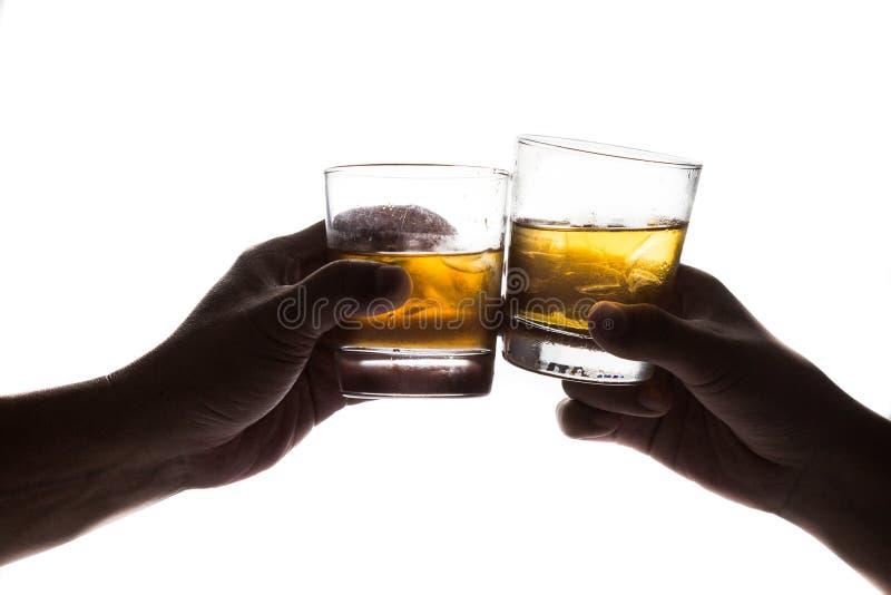 Silhouette de deux mains grillant le whiskey sur la roche avec le fond blanc images stock