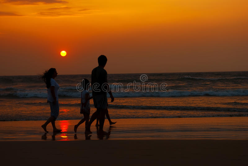 Silhouette de famille marchant le long de la côte images stock