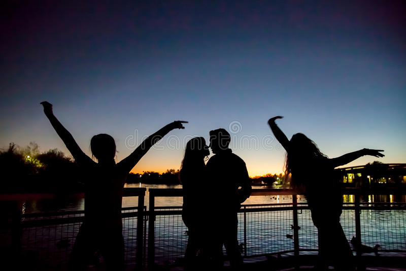 Silhouette de famille par le lac photos libres de droits