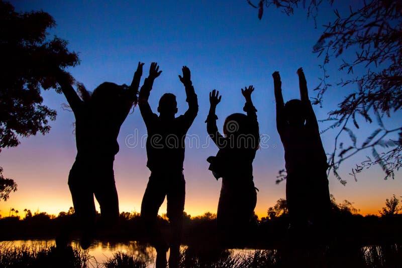 Silhouette de famille sautante images stock