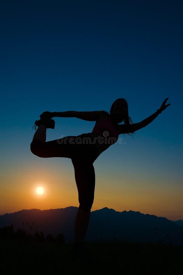 Silhouette de femme au coucher du soleil photo stock
