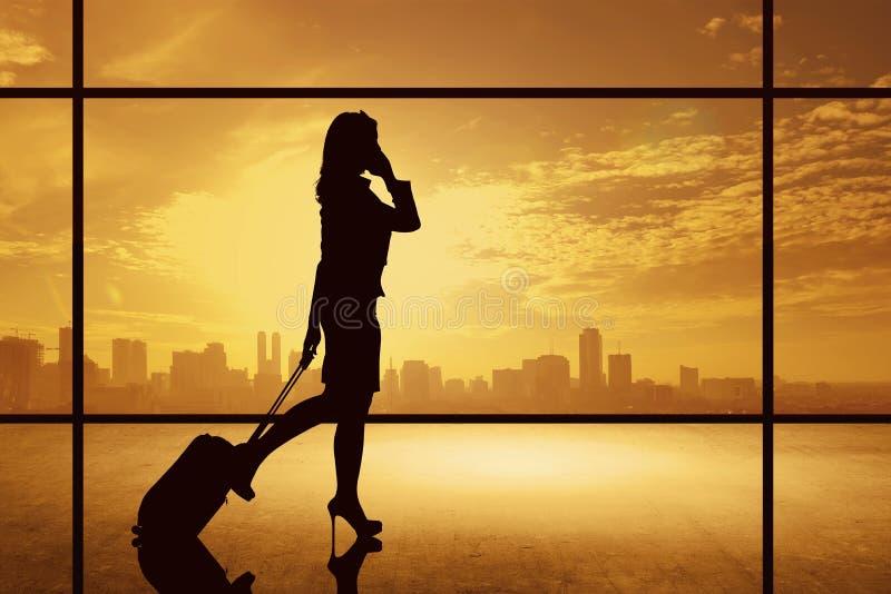 Silhouette de femme d'affaires marchant avec la valise photos stock