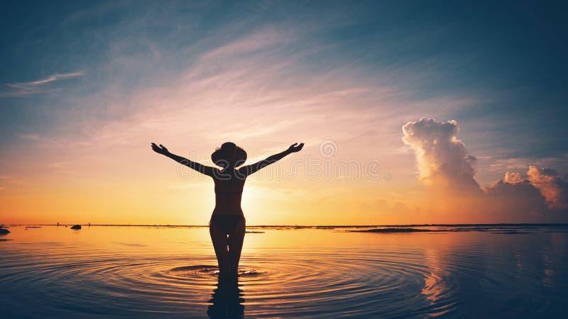 Silhouette de femme dans l'océan au coucher du soleil photo libre de droits