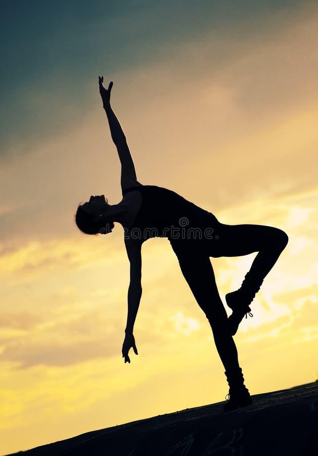 Silhouette de femme de danse au-dessus de coucher du soleil. Yoga photos stock
