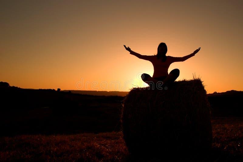 Silhouette de femme effectuant le yoga images libres de droits