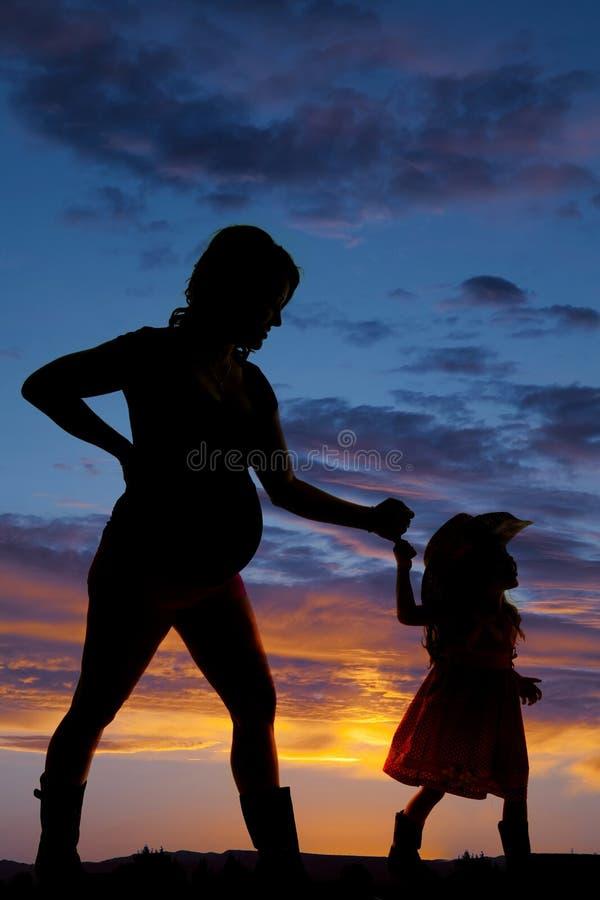 Silhouette de femme enceinte se tenant avec une cow-girl d'enfant en bas âge image stock