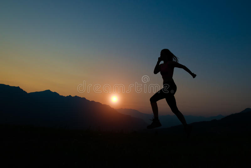 Silhouette de femme fonctionnant au coucher du soleil photo stock