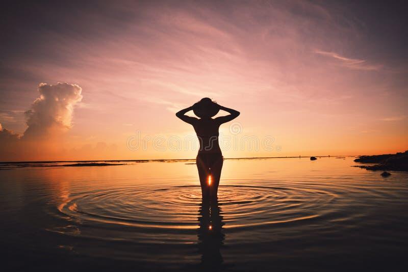 Silhouette de femme gaie dans le coucher du soleil de réunion d'océan image stock