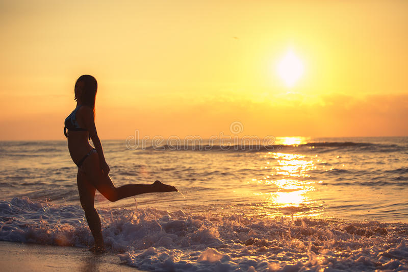 Silhouette de femme insouciante sur la plage photo libre de droits