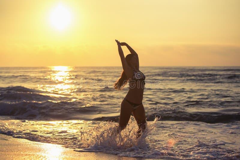 Silhouette de femme insouciante sur la plage images libres de droits