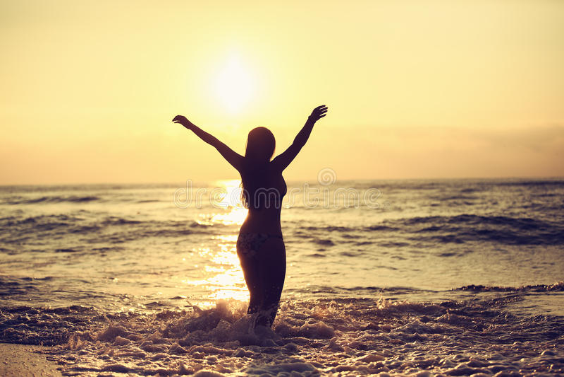 Silhouette de femme insouciante sur la plage image stock