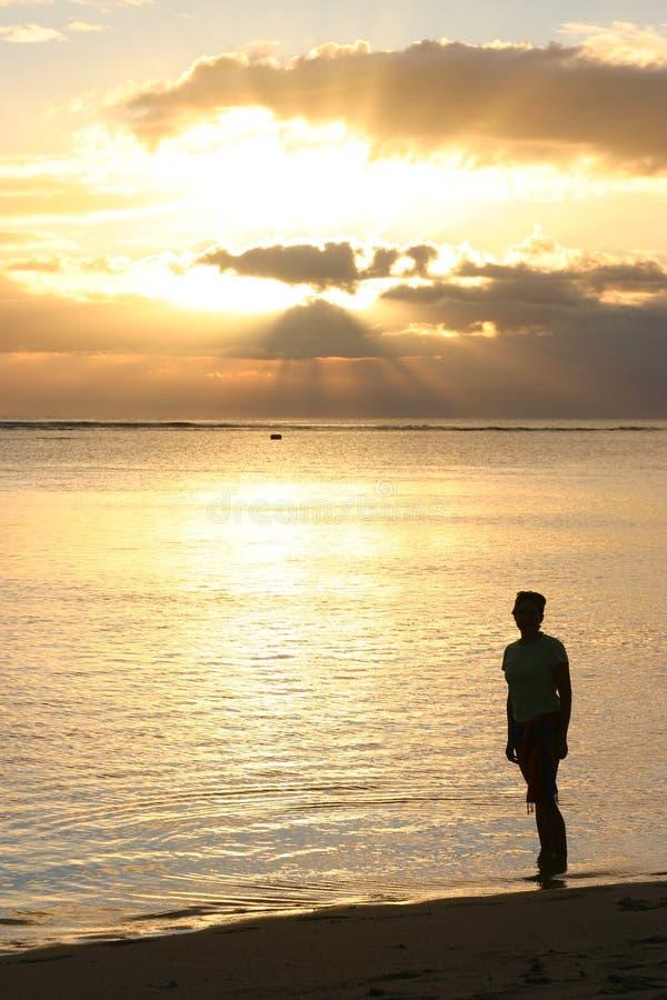 Silhouette de femme observant le coucher du soleil image stock