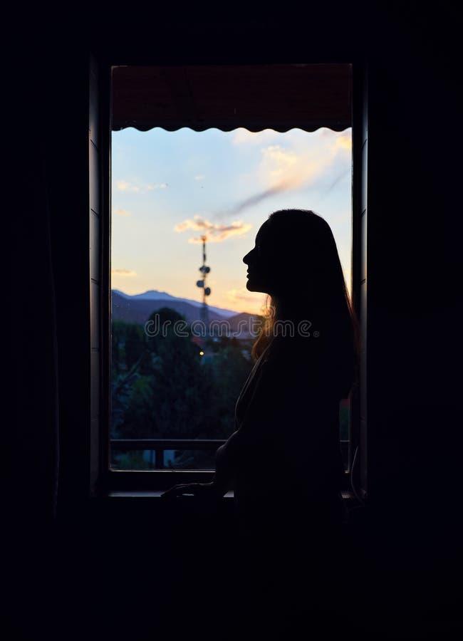 Silhouette de femme près de fenêtre photos stock