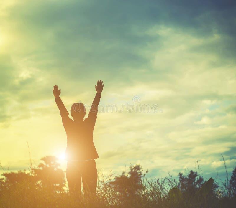 Silhouette de femme priant au-dessus du beau fond de ciel photos libres de droits