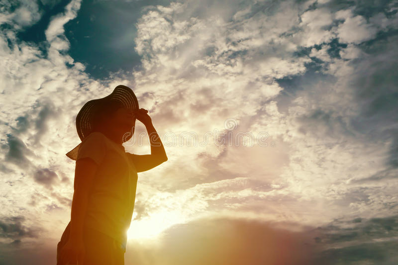Silhouette de femme regardant au ciel le temps de coucher du soleil image stock