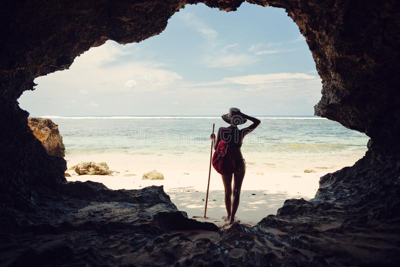 Silhouette de femme se tenant en caverne sur la plage et regardant loin photos stock