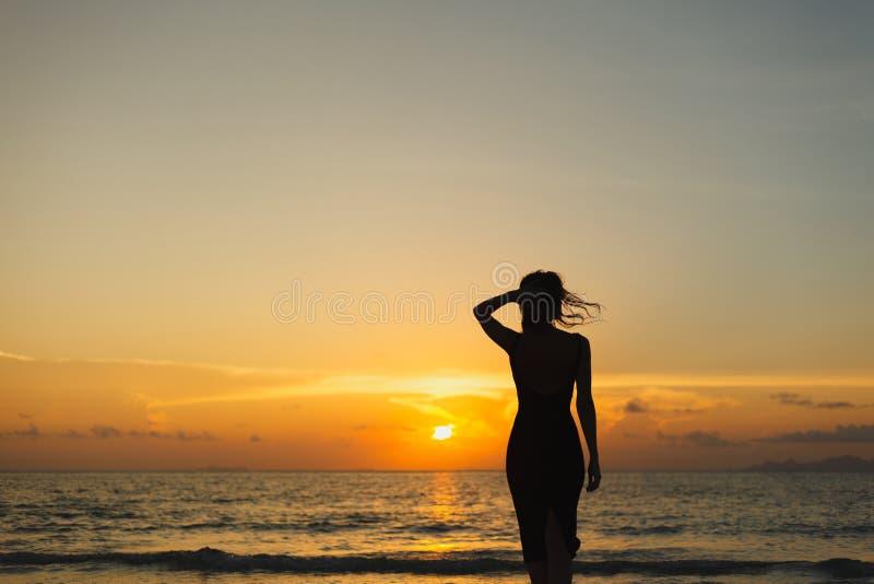 silhouette de femme se tenant sur la plage d'océan et regardant loin pendant le coucher du soleil photo stock