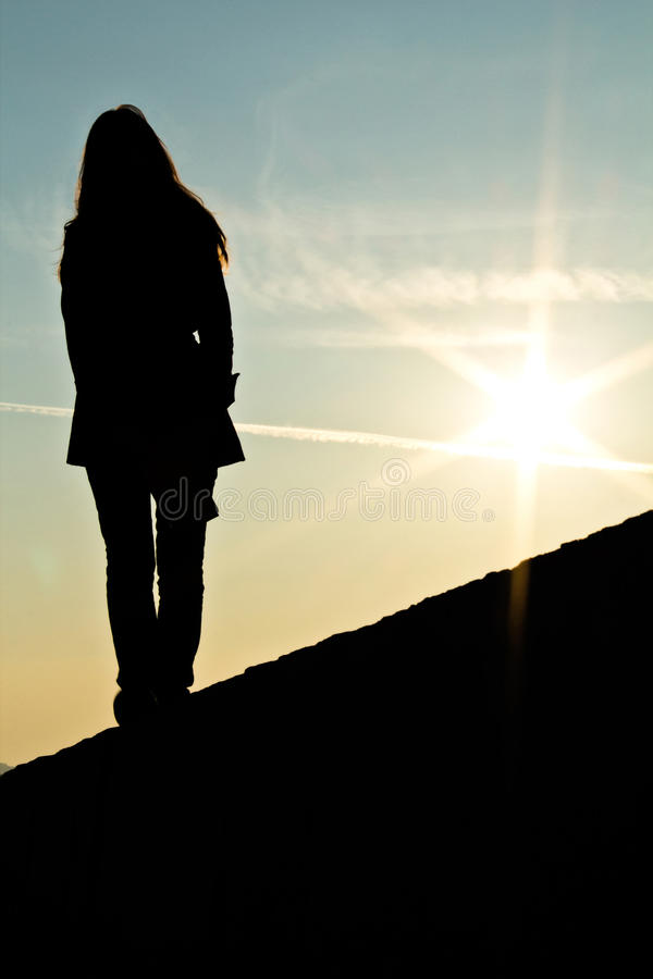 Silhouette de femme se tenant sur un mur dans le beau coucher du soleil photographie stock