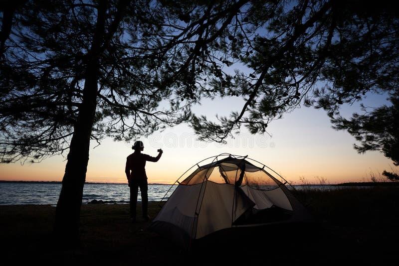 Silhouette de femme sur le bord de mer pr?s de la tente de touristes avec l'appareil-photo de photo, prenant la photo images libres de droits