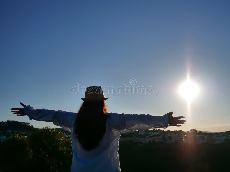 Silhouette de fille de brune dans la chemise et le chapeau sur le fond du lever de soleil, copyspace photos stock