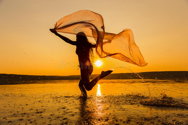 Silhouette de fille fonctionnant sur la plage photos libres de droits
