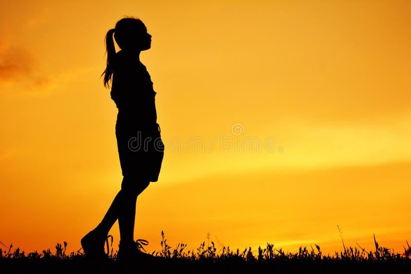Silhouette de fille heureuse se tenant sur le champ d'herbe image libre de droits