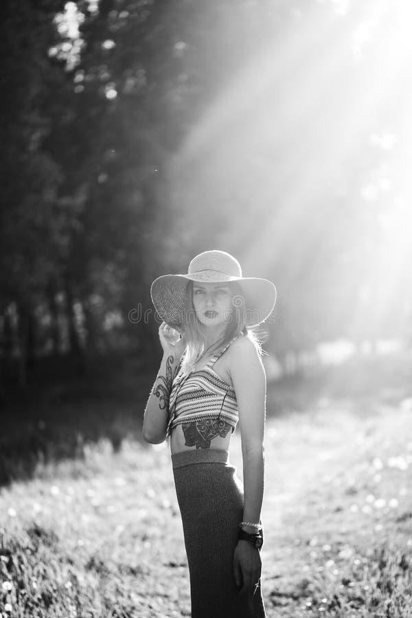 Silhouette de fille marchant en parc extérieur Concept ensoleillé de mode de vie d'été Femme dans la robe et le chapeau dans le d image stock