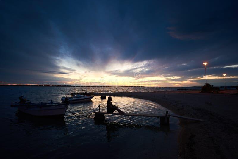Silhouette de fille mince se reposant sur le pont en bois étroit à de petits canots automobiles au coucher du soleil photographie stock
