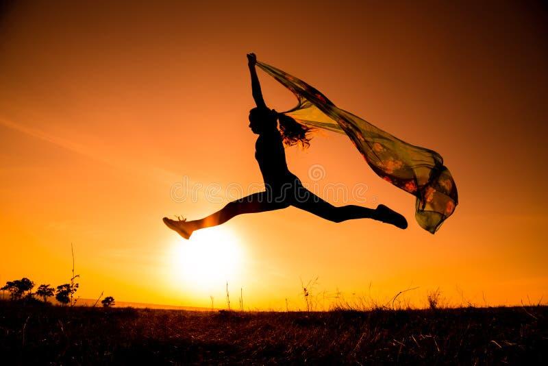 Silhouette de fille sautante contre le coucher du soleil photographie stock