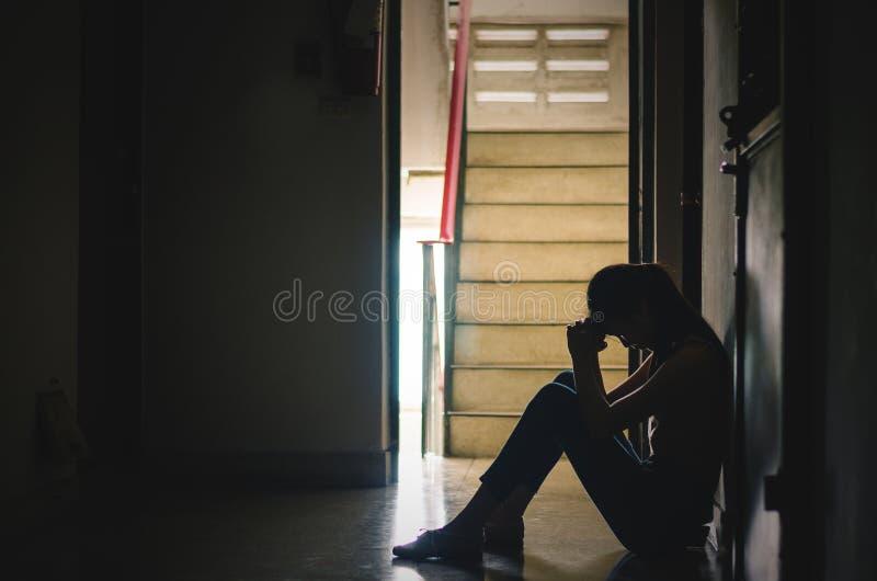Silhouette de fille se reposant seul, tristes et sérieuses femmes s'asseyant pour étreindre son seul genou de logement étroit , M photo libre de droits