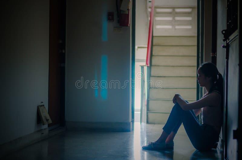 Silhouette de fille se reposant seul, tristes et s?rieuses femmes s'asseyant pour ?treindre son seul genou de logement ?troit , M image stock